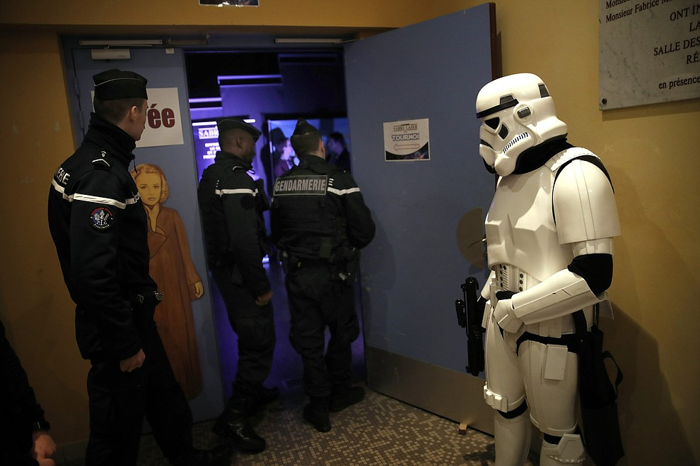 In this Sunday, Feb. 10, 2019, photo, a man dressed up as Stormtrooper and French gendarmes watch a national lightsaber tournament in Beaumont-sur-Oise, north of Paris. (AP Photo/Christophe Ena)