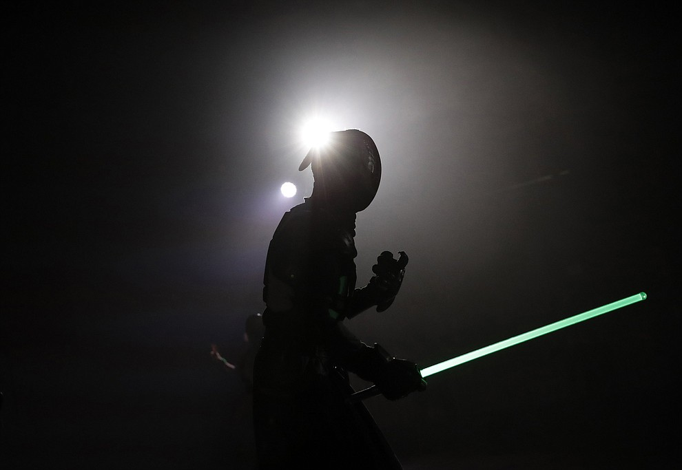 In this Sunday, Feb. 10, 2019, photo, a competitor battles during a national lightsaber tournament in Beaumont-sur-Oise, north of Paris. (AP Photo/Christophe Ena)