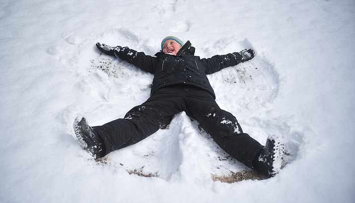 Kenna Teagan, from Phoenix, makes a snow angel with her parents at Lynx Lake Monday, Feb. 18, 2019 in the Prescott National Forest. The lake received about 3 inches of snow overnight from the fast moving storm. More snow is expected from a stronger storm on Thursday into Friday this week. (Les Stukenberg/Courier)