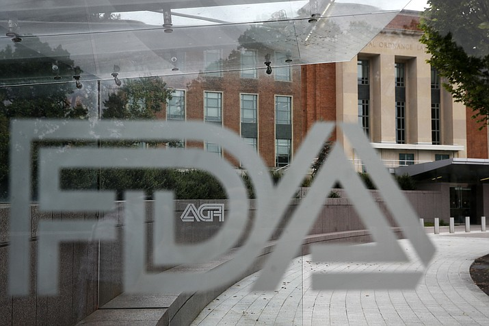 This Aug. 2, 2018 file photo shows the U.S. Food and Drug Administration building behind FDA logos at a bus stop on the agency's campus in Silver Spring, Md. A federal judge has slapped down efforts by the Goldwater Institute to force the Food and Drug Administration to detail publicly how dying people can get access to unapproved medicines.