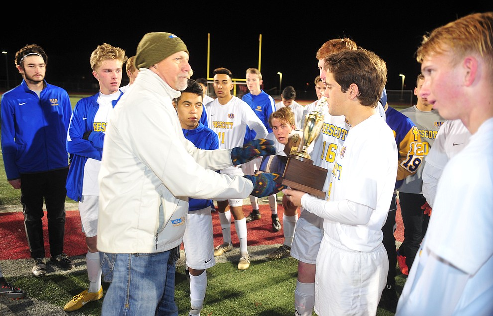 Dean Visser presents the runnerup trophy to Prescott's Nathaniel Koehler after the Badgers lost to the Salpointe Catholic Lancers in the Arizona Interscholastic Association 4A State Soccer Championship Tuesday, February 19, 2019 at Williams Field High School in Gilbert. (Les Stukenberg/Courier).