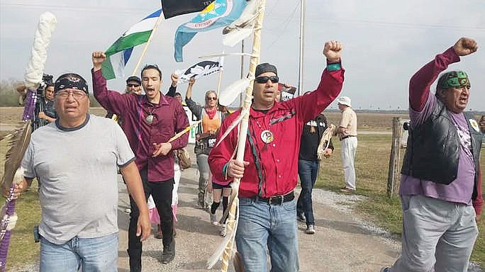 Juan Mancias, chairman of the Carrizo/Camecrudo Tribe (far right) and supporters from the Standing Rock Sioux Tribe, environmental groups, and others march in South Texas against the impending construction of the border wall through ancestral Native land. (Screenshot of a video by Gus Bova. Used with permission via Indian Country Today)