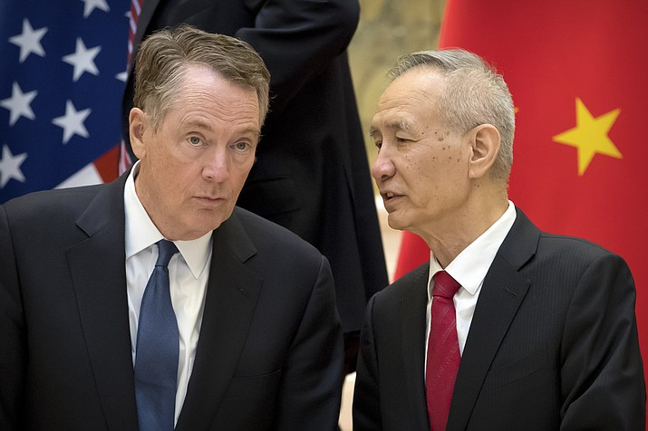 Chinese Vice Premier Liu He, right, talks with U.S. Trade Representative Robert Lighthizer, while they line up for a group photo Feb. 15, 2019, at the Diaoyutai State Guesthouse in Beijing. China's economy czar is going to Washington for talks Thursday and Friday aimed at ending a tariff war over Beijing's technology ambitions.(Mark Schiefelbein/AP, File)