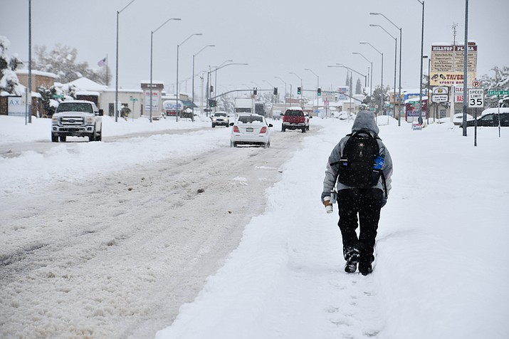 A Kingman resident braves the snow storm and walks down Stockton Hill Road early Thursday afternoon. (Photo by Vanessa Espinoza/Daily Miner)