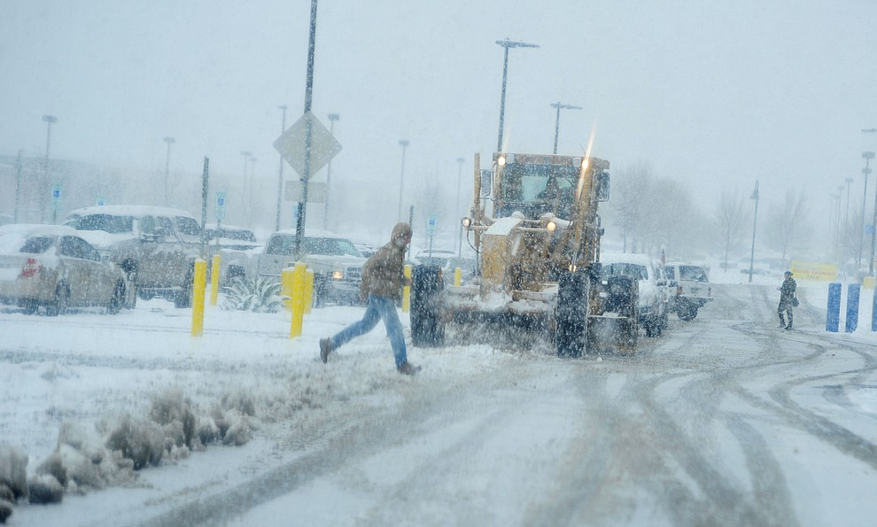 A grader clears the Walmart parking lot as shoppers dash inside as the predicted snowfall Thursday, Feb. 21, 2019 hit the Prescott Valley area. (Les Stukenberg/Courier).
