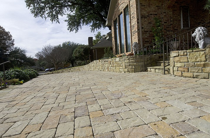 This 2018 photo shows a stone pavers driveway in a residential neighborhood in Dallas, Texas. One driveway at a time, many homeowners and communities are opting for permeable paving options instead of traditional asphalt. (AP Photo/Benny Snyder)