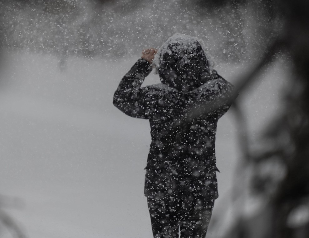Woman taking a photo out in the snow. Shot in Prescott near PHS on 2/21/2019 (Dagny Gromer)