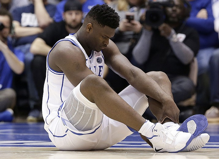 Duke's Zion Williamson sits on the floor following a injury during the first half of an NCAA college basketball game against North Carolina in Durham, N.C., Wednesday, Feb. 20, 2019. (Gerry Broome/AP)