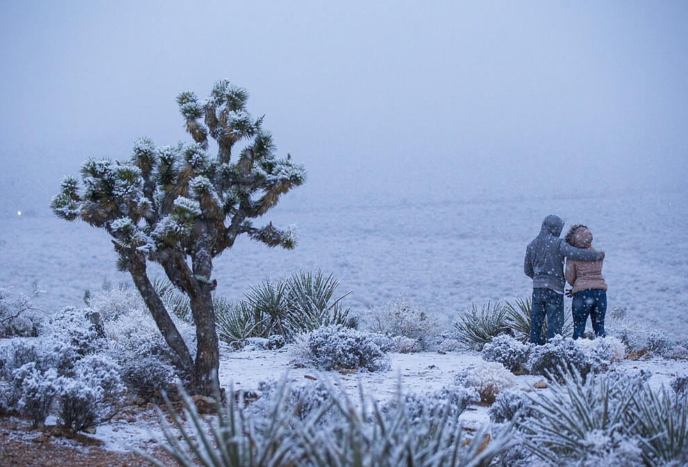 James Minner, of Las Vegas, left, and Candace Reid, of Albuquerque, N.M., watch as snow falls around the overlook at the Red Rock Canyon National Conservation Area outside of Las Vegas on Wednesday, Feb. 20, 2019. (Chase Stevens/Las Vegas Review-Journal via AP)