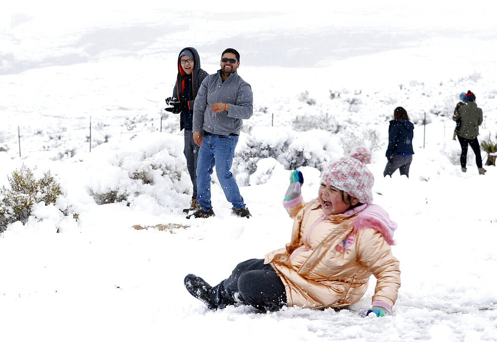Valentina Gonzalez, 7, laughs after falling during a snowball fight with her family at the Red Rock Canyon National Conservation, west of Las Vegas Thursday, Feb. 21, 2018. In the background is her father Omar Gonzalez and her brother Omar Jr.  (Steve Marcus/Las Vegas Sun via AP)