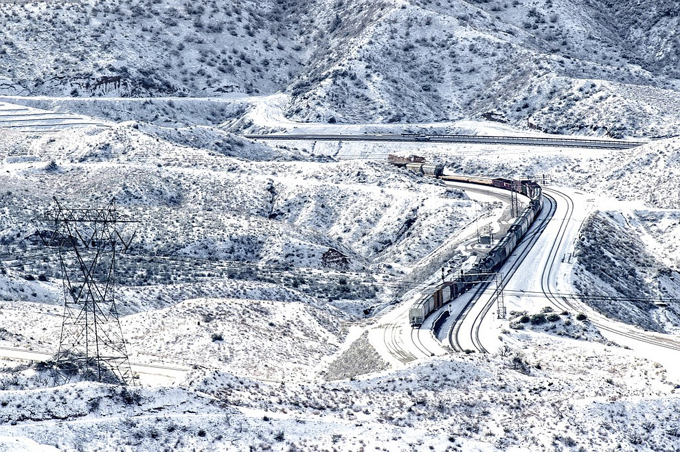 A train rolls along the snow covered hills in the Cajon Pass near Highway 138 in Phelan, Calif., Thursday, Feb. 21, 2019. (Watchara Phomicinda/The Orange County Register via AP)