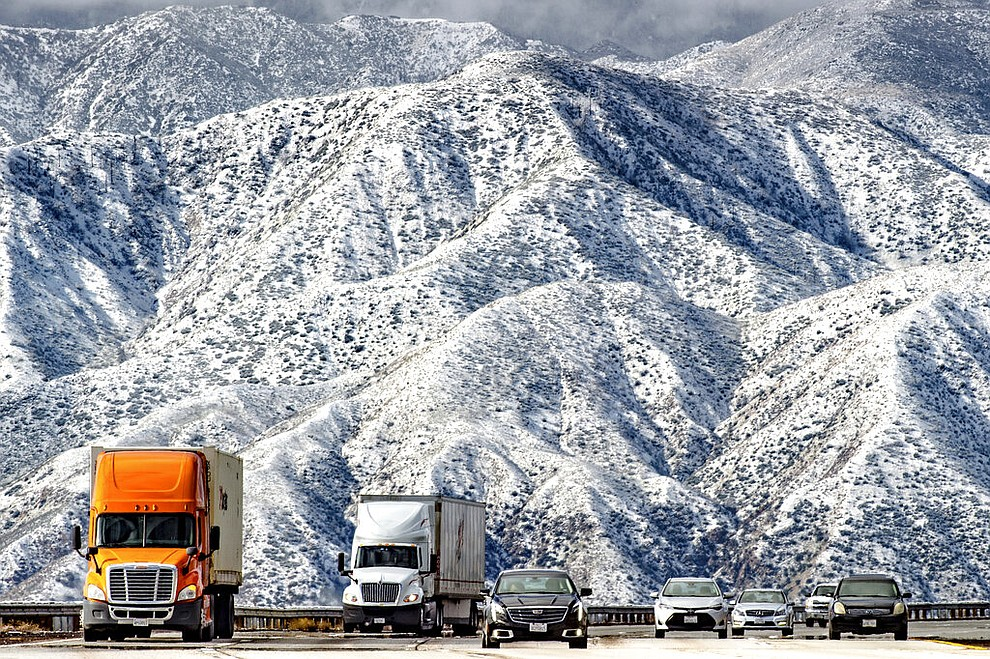 Mountains are blanketed with snow as traffic makes its way slowly through Cajon Pass on the I-15 near Hwy 138 in Phelan, Calif., Thursday, Feb. 21, 2019. (Watchara Phomicinda/The Orange County Register via AP)