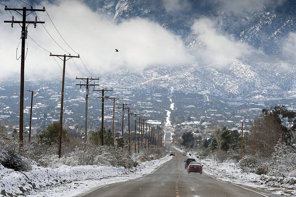 Cars roll down Oasis Road following a fresh snowfall in Pinon Hills Calif., Thursday, Feb. 21, 2019. (James Quigg/The Daily Press via AP)