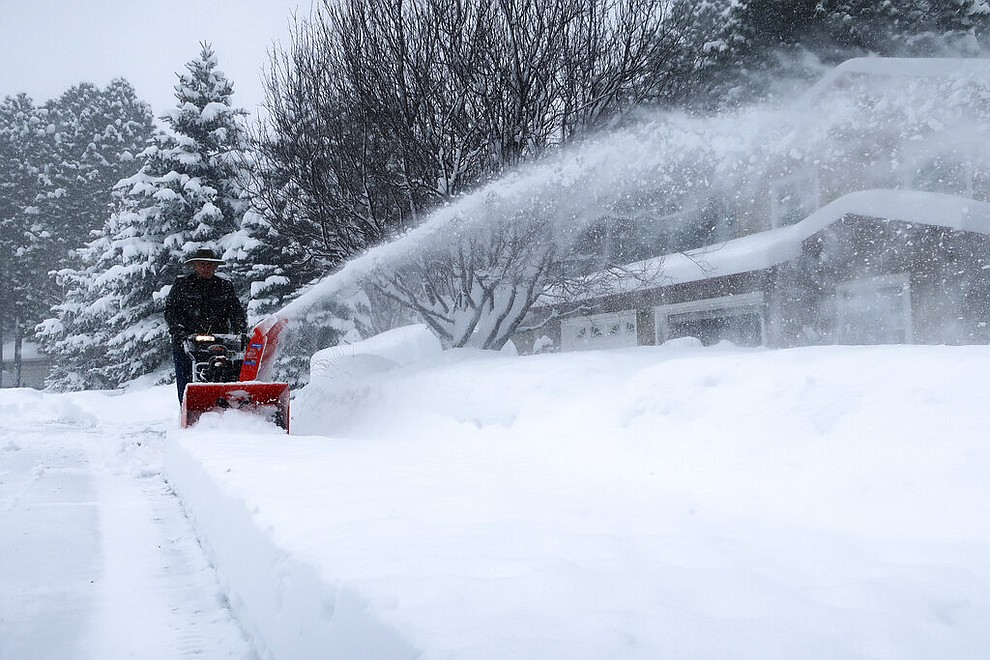 Richard Henn runs a snow blower down the sidewalk outside his home in Flagstaff, Arizona, on Thursday, Feb. 21, 2019. Schools across northern Arizona canceled classes and some government offices decided to close amid a winter storm that's expected to dump heavy snow in the region. (AP Photo/Felicia Fonseca)