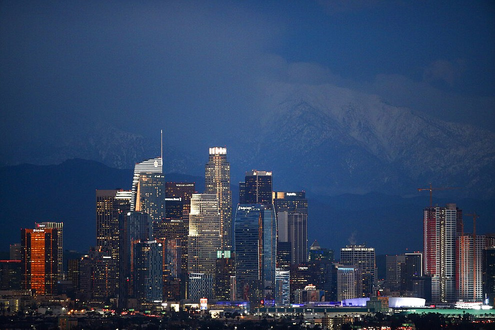 Snow-capped mountains are seen behind the Los Angeles' downtown skyline at dusk Thursday, Feb. 21, 2019, in Los Angeles. (AP Photo/Jae C. Hong)