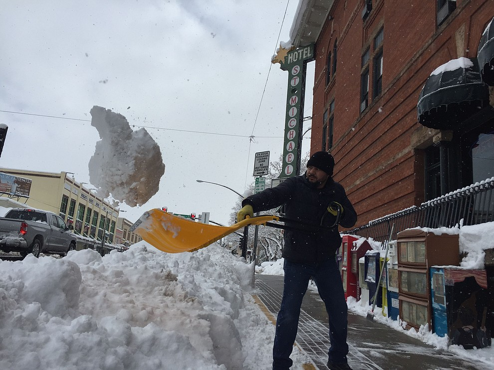 Hotel St. Michael's head of maintenance clears the sidewalks in front of the business in downtown Prescott Friday morning, Feb. 22. (Max Efrein/Courier)