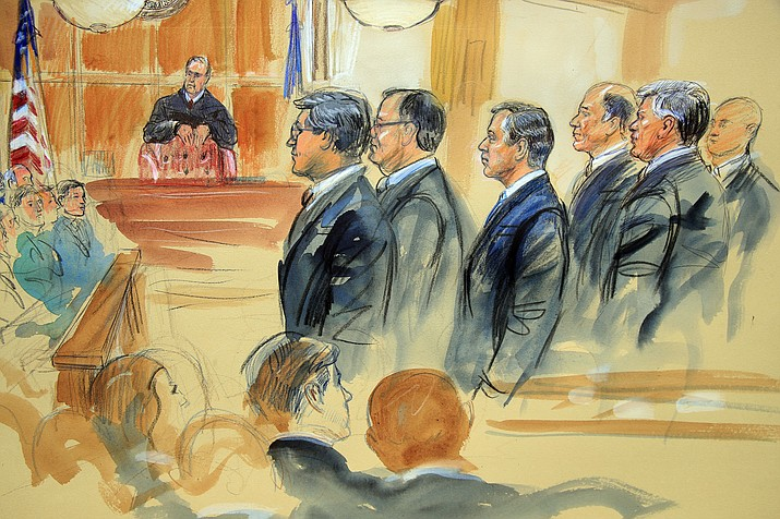This July 2018 courtroom sketch depicts Paul Manafort, fourth from right, standing with his lawyers in front of U.S. district Judge T.S. Ellis III, center rear, at the Alexandria Federal Courthouse in Alexandria, Va. Ellis has set a March 8, 2019, sentencing date for Manafort on his Virginia conviction for hiding millions of dollars from the IRS that he earned advising Ukrainian politicians. The order means Manafort will face sentencing in Virginia before he does in the District of Columbia. His sentencing in the District has already been set for March 13. (Courtroom sketch by Dana Verkouteren)