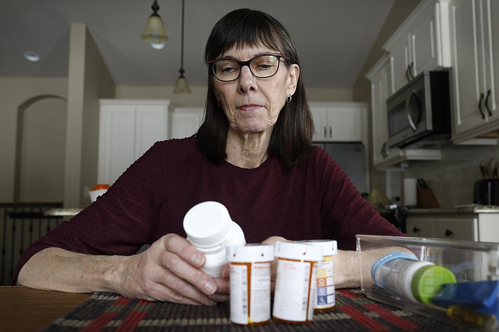 Retired public school teacher Gail Orcutt, of Altoona, Iowa, looks over some of the prescription drugs she takes, Friday, Feb. 15, 2019, in Altoona, Iowa. Orcutt pays $2,600 the first month of the year, and then $750 every other month for a lung cancer medication. With health care a top issue for American voters, Congress may actually be moving toward doing something this year to address the high cost of prescription drugs. (Charlie Neibergall/AP)