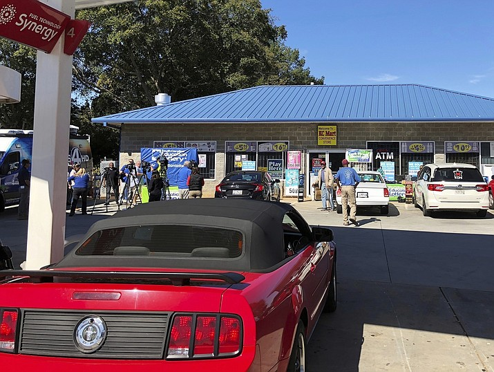 In this Wednesday, Oct. 24, 2018 file photo, media, at left, record people entering the KC Mart in Simpsonville, S.C., after it was announced the winning Mega Millions lottery ticket was purchased at the store. Nearly everyone in this small town has a theory for the city's billion-dollar mystery: Who won the $1.5 billion Mega Millions jackpot announced last October? (Jeffrey Collins/AP, file)
