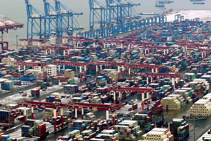 "In this Feb. 14, 2019, photo, trucks move around containers stored at a port in Qingdao in east China's Shandong province. U.S. President Donald Trump said Sunday, Feb. 24, 2019, he will extend a deadline to escalate tariffs on Chinese imports, citing ""substantial progress"" in weekend talks between the two countries. (Chinatopix via AP)"