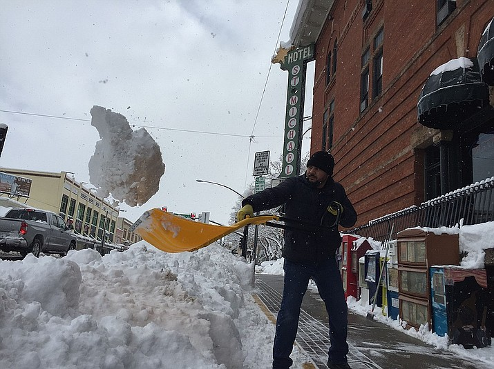 Hotel St. Michael's head of maintenance clears the sidewalks in front of the business in downtown Prescott Friday, Feb. 22. (Max Efrein/Courier)