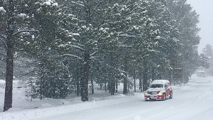 A vehicle navigates snowpacked roads at Grand Canyon National Park Feb. 22 after a winter storm blanketed the park with about a foot of snow. (Photo/NPS)