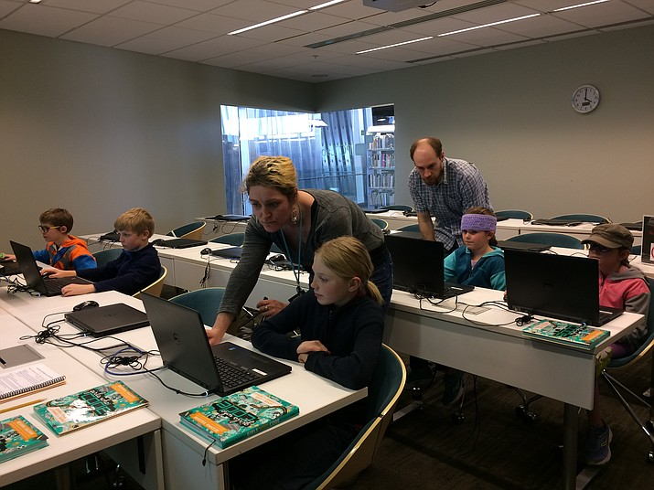 The Girls (and Boys) Who Code class meets at the Prescott Valley Public Library on Monday afternoons. From left are Gabriel Maroni, 8, Blain Priest, 9, Assistant Teen Librarian Coleen Bornschlegel helping Aidan Priest, 10, Assistant Children's Librarian Jeff Howick helping Ruby Jakes, 6, and Mabel Jakes, 8. (Sue Tone/Tribune)