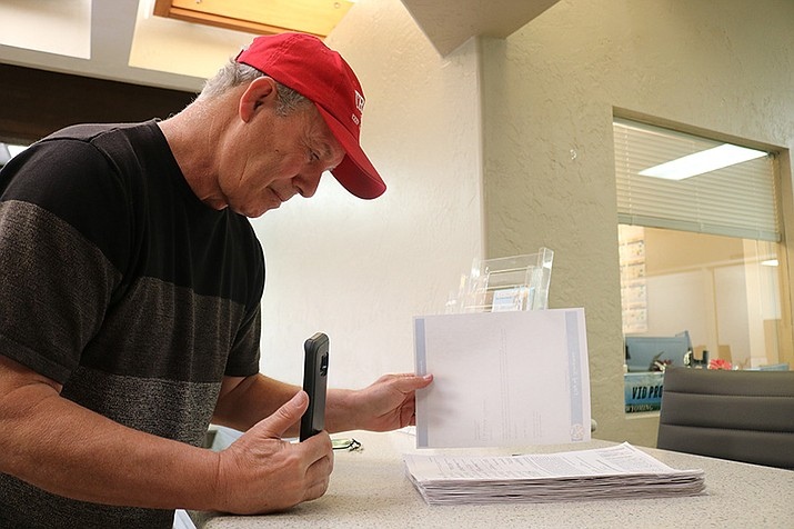 Steve Robinson, chair of Kingman Citizens for Honesty, Accountability and Transparency, picks up the 1,058 signatures he gave the City Monday. Those signatures were returned Tuesday as they did not meet the 1,946 threshold. (Photo by Travis Rains/Daily Miner)