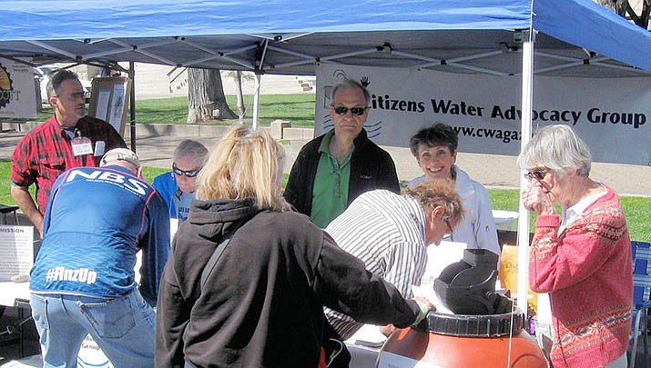 CWAG members, from left, Michael Adcock, Cheryl Hill, Art Manburg, Delores Manburg and Dianne Oswald work the organization's tent in April 2017 at Earth Day. The orange rain barrel was donated by C-A-L Ranch and the diverter by CWAG. The barrel and diverter CWAG ius giving away again are the same as pictured. (Fred Oswald/Courtesy)