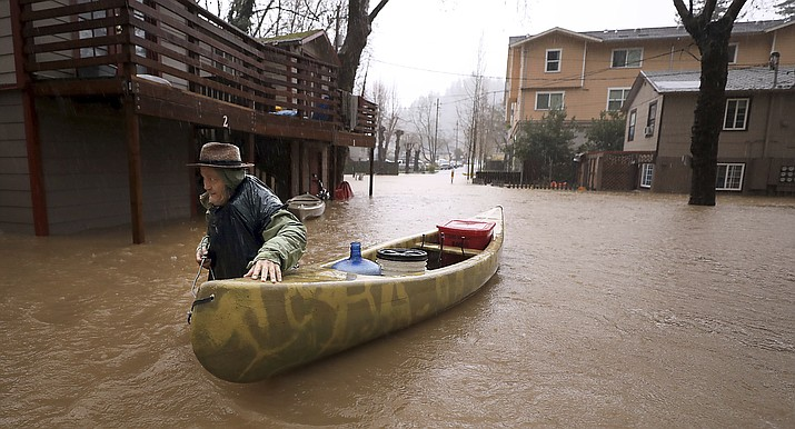 Sycamore Court resident Jesse Hagan evacuates to higher ground in the apartment complex in lower Guerneville, Calif., Tuesday, Feb. 26, 2019. (Kent Porter/The Press Democrat via AP)