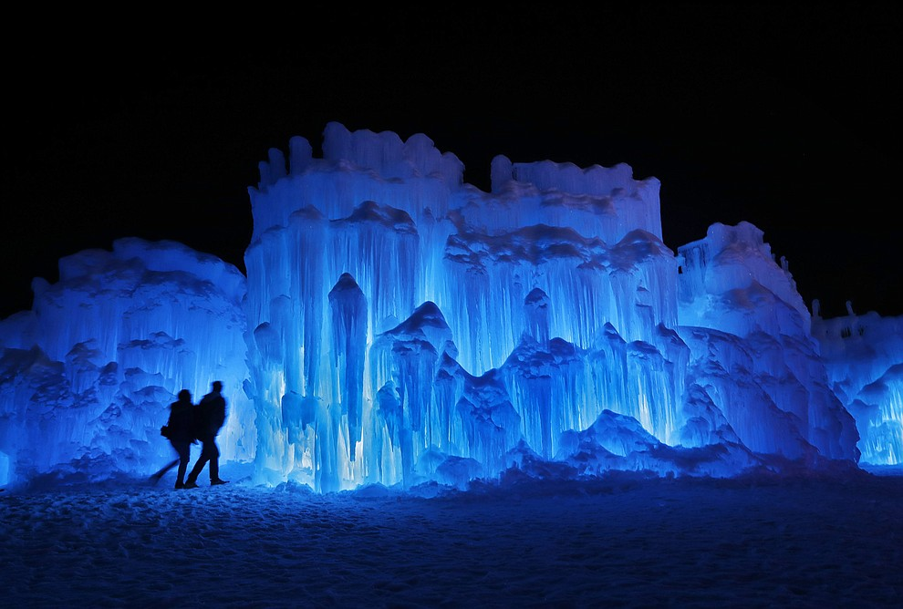 In this Saturday, Jan. 26, 2019 photo, a couple heads towards an entrance to a cavern at Ice Castles in North Woodstock, N.H. A team starts building massive walls in December to create a spectacular winter experience. (AP Photo/Robert F. Bukaty).