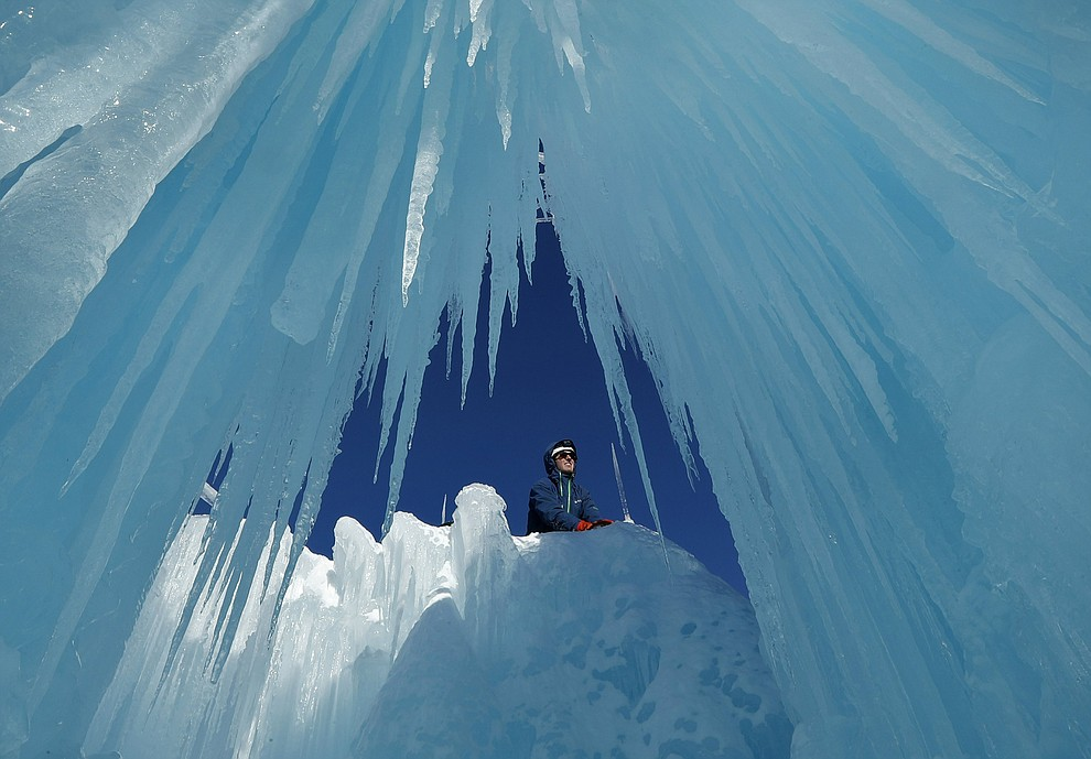 In this Monday, Jan. 28, 2019 photo, Matt Pasciuto places an icicle at the top of a wall at Ice Castles in North Woodstock, N.H. Slushy snow is used as quick-freezing mortar to hold icicles in place. The spray from sprinklers will help grow the icicles into walls and caverns. (AP Photo/Robert F. Bukaty).