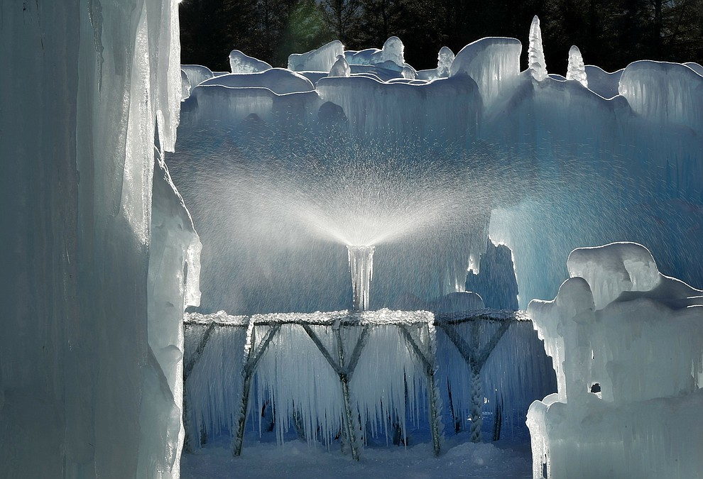 In this Monday, Jan. 28, 2019 photo, a sprinkler sprays a fine mist over a metal rack to grow icicles at Ice Castles in North Woodstock, N.H. Ice artists will harvest the icicles and use them to grow the castles' walls. (AP Photo/Robert F. Bukaty).