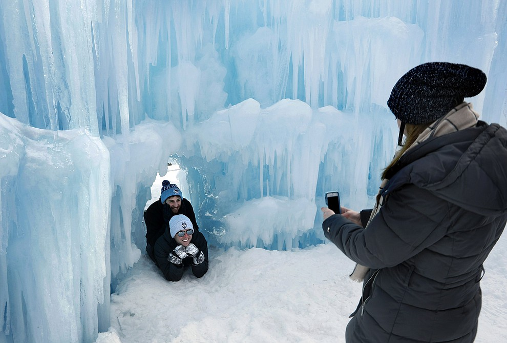 In this Saturday, Jan. 26, 2019 photo, visitors pose for a photo in a tunnel at Ice Castles in North Woodstock, N.H. With a seemingly endless variety of photo-ops, most visitors have a hard time putting their cameras down. (AP Photo/Robert F. Bukaty).