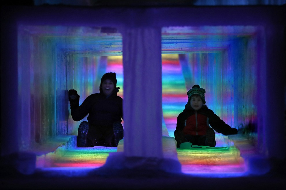 In this Friday, Jan. 25, 2019 photo, visitors race down the side-by-side tunnels of a 97-foot ice slide at Ice Castles in North Woodstock, N.H. The winter wonderland is one of six in North America. (AP Photo/Robert F. Bukaty).