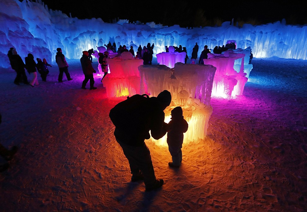 In this Saturday, Jan. 26, 2019 photo, Bruce McCafferty and his son, Dougie, pause while exploring the ice formations growing at Ice Castles in North Woodstock, N.H. (AP Photo/Robert F. Bukaty).
