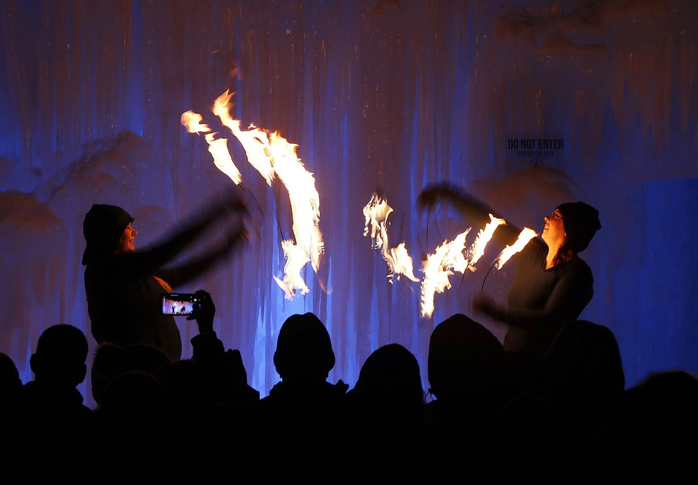 In this Friday, Jan. 25, 2019 photo, fire dancers perform at Ice Castles in North Woodstock, N.H. The winter wonderland is one of six in North America. (AP Photo/Robert F. Bukaty).