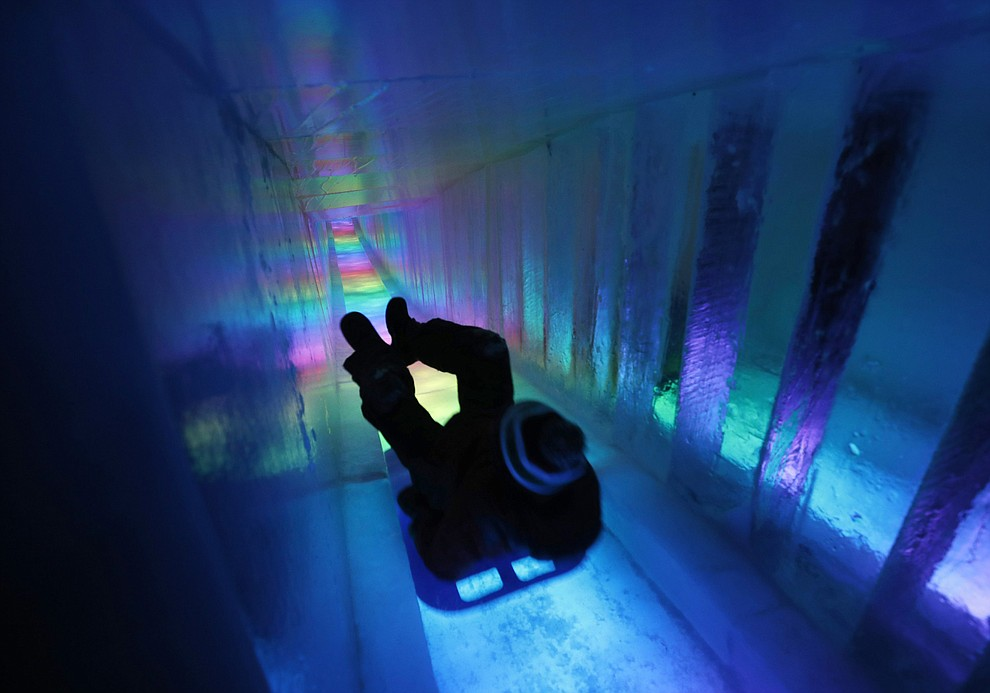 In this Saturday, Jan. 26, 2019 photo, a man zooms down a 97-foot ice slide at Ice Castles in North Woodstock, N.H. (AP Photo/Robert F. Bukaty).