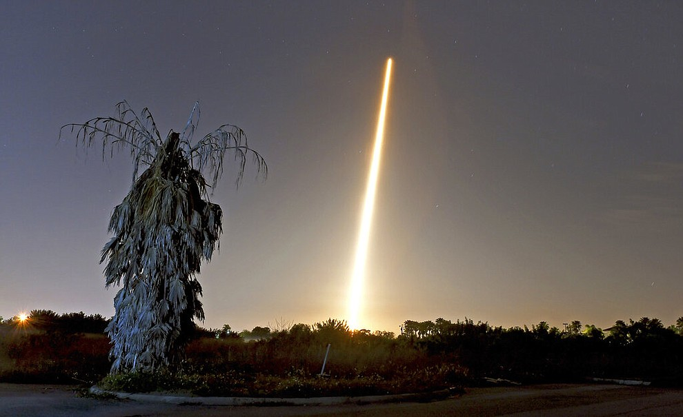 The SpaceX Falcon 9 rocket and Crew Dragon capsule launch from NASA pad 39A as seen in a time exposure from Viera, FL. on March 2 with a lone, untrimmed palm tree in the foreground. (Tim Shortt/Florida Today via AP)