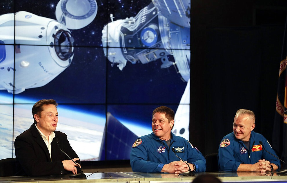 Elon Musk, left, CEO of SpaceX, speaks as NASA astronauts Bob Behnken, center, and Doug Hurley, right, listen during a news conference after the SpaceX Falcon 9 Demo-1 launch at the Kennedy Space Center in Cape Canaveral, Fla., Saturday, March 2, 2019. (AP Photo/John Raoux)