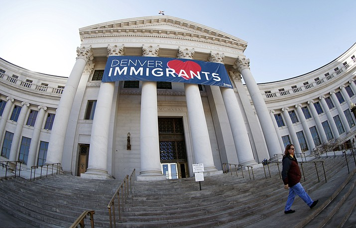 "A banner to welcome immigrants is shown through a fisheye lens over the main entrance to the Denver City and County Building on Feb. 26, 2018. The U.S. Justice Department told The Associated Press at the end of February 2019 that 28 jurisdictions, including Denver, that were targeted in 2017 over what it considered ""sanctuary"" policies have been cleared for law enforcement grant funding. (David Zalubowski/AP, File)"