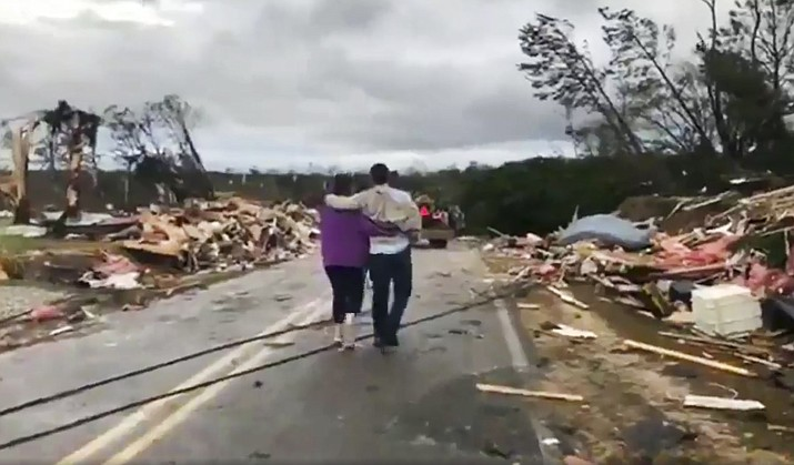 People walk amid debris in Lee County, Ala., after what appeared to be a tornado struck in the area Sunday, March 3, 2019. Severe storms destroyed mobile homes, snapped trees and left a trail of destruction amid weather warnings extending into Georgia, Florida and South Carolina, authorities said. (WKRG-TV via AP)