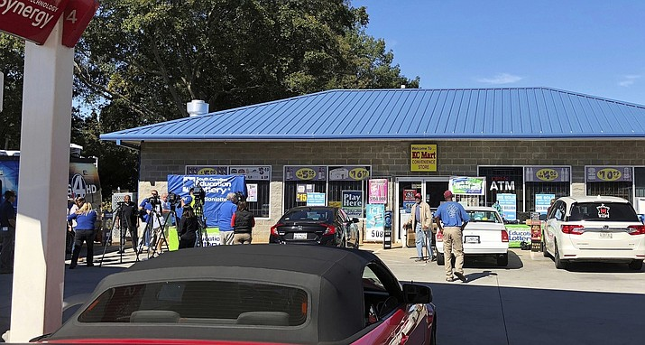 In this Oct. 24, 2018, file photo, media, at left, record people entering the KC Mart in Simpsonville, S.C., after it was announced the winning Mega Millions lottery ticket was purchased at the store. The South Carolina lottery says a single winner has stepped forward to claim the $1.5 billion Jackpot from a drawing last October. A lottery commission statement says the person submitting the claim for what was the second-largest lottery in U.S. history has chosen to remain anonymous. (Jeffrey Collins/AP, File)
