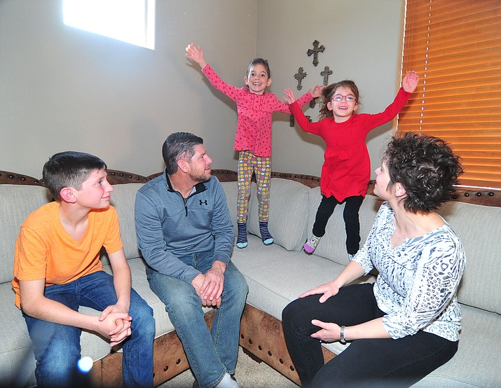 Dana and Brian Eisenhour with their children Jacob, 9, and their two adopted daughters, Odyssey, 5, and Taylynn, 4 at their home in Dewey-Humboldt Thursday, Feb. 28, 2019.  The Eisenhour's adopted sisters Odyssey and Taylynn about a year ago. (Les Stukenberg/Courier)