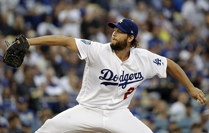 In this Oct. 28, 2018, file photo, Los Angeles Dodgers pitcher Clayton Kershaw winds up to throw during the first inning in Game 5 of the World Series baseball game against the Boston Red Sox in Los Angeles. Dodgers manager Dave Roberts says Kershaw is making steady progress in his recovery from left shoulder inflammation, but the ace may not be ready to start opening day. (David J. Phillip/AP, file)