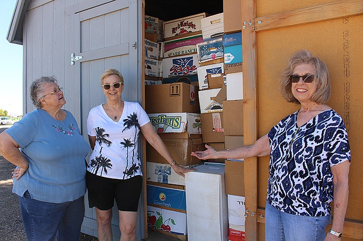 From left, Mary Griffis, Yvonne Decker and Gloria Dunkel stand outside a shed full of boxes of books offered for sale at the book sale Friday and Saturday. (Daily Miner file photo)
