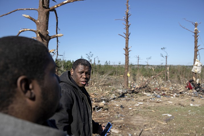 Demetria Jones, right, and his cousin Cordarrly Jones, walk through the damaged neighborhood where they said they lost ten relatives in a tornado in Beauregard, Ala., Tuesday, March 5, 2019. (AP Photo/David Goldman)