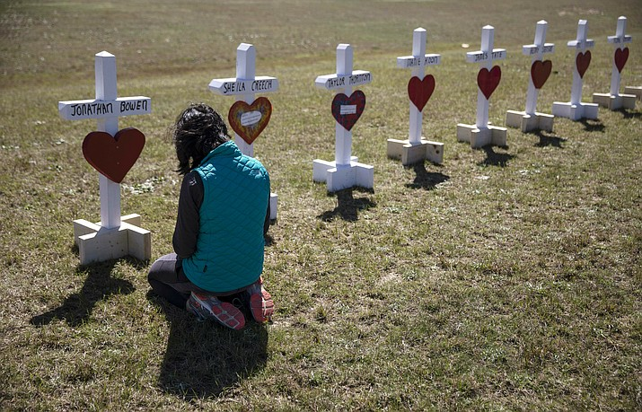 "Jessica Taylor prays in front of a cross for Jonathan Bowen, 9, at a makeshift memorial for the victims of a tornado in Beauregard, Ala., Wednesday, March 6, 2019. ""I have a son his age,"" said Taylor. ""I can't imagine that mother's loss."" (David Goldman/AP)"