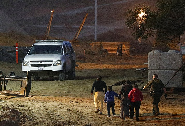 In this Dec. 3, 2018, file photo, migrants are escorted by a U.S. Border Patrol agent as they are detained after climbing over the border wall from Playas de Tijuana, Mexico, to San Ysidro, Calif. The Trump administration's effort to make asylum seekers wait in Mexico explicitly targets Spanish-speakers and people from Latin America, according to internal guidelines of a highly touted strategy to address the burgeoning number of Central Americans arriving at U.S. borders. (AP Photo/Rebecca Blackwell, File)