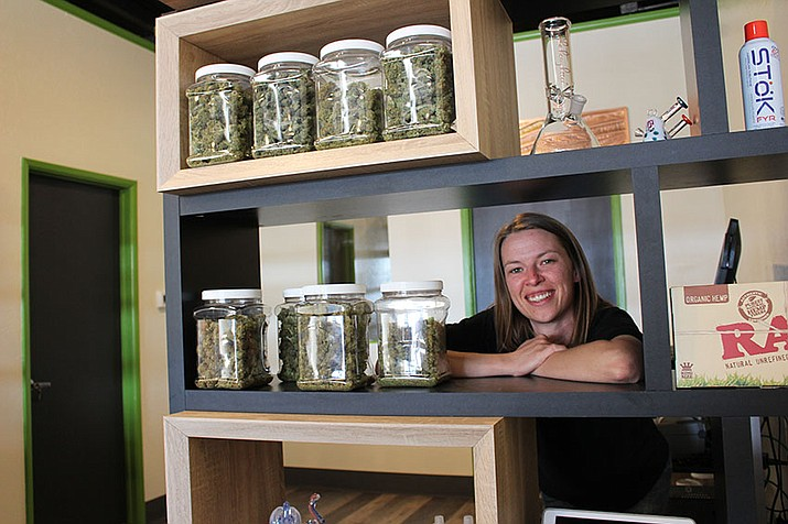 Stephanie Cronin, manager of Medusa Farms Dispensary, shows a variety of medical marijuana products available at the dispensary at 3358 Andy Devine Ave. in this May 6, 2018 file photo. A poll shows Arizonans are more and more supporting legalizing marijuana for recreational use. (Daily Miner file photo)
